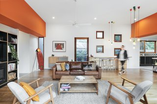 Two dividing orange bulkheads—which are the box gutters that protrudes through the house—separate the three pavilions. The family congregates in the central pavilion for meals around the dining table, and to relax in the lounge.