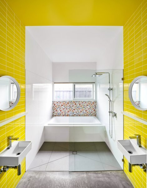 The majority of the boys' bathroom is clad in economic, white ceramic tile. A band of yellow tiles delineates each boy's personal area, and the color continues across the ceiling. The Andy Warhol pixelated tiles by Dune were an indulgence, and they were used sparingly for impact.