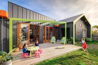 The home is divided into three distinct pavilions. Orange box gutters break up these three forms, and a green pergola unites them. Instead of downpipes, rain chains are used as a visual element.