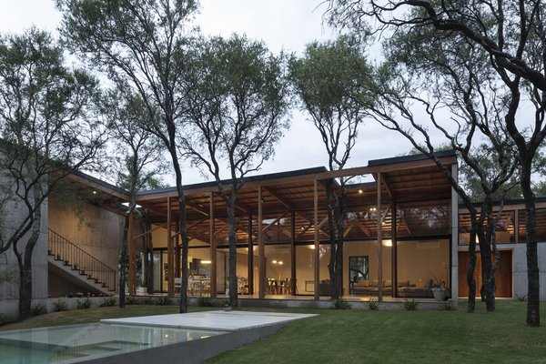 The large social space at the center of the home opens out to views of the surrounding trees and the pool.