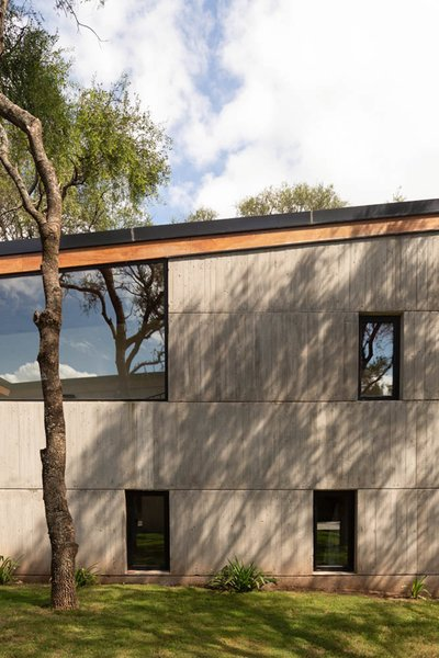 The concrete walls are perforated by large and small windows that frame views of the trees and local forest, as the site doesn't offer expansive views of the surrounding landscape.