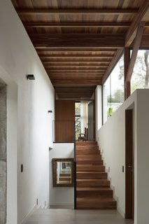 Timber stairs lead from the entrance block up to the master bedroom.