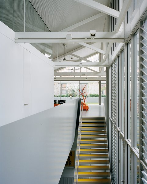 """The stair treads are finished with bright yellow cork tiles. """"The clients were comfortable with the introduction of as much color as possible,"""" says architect Ian Moore."""