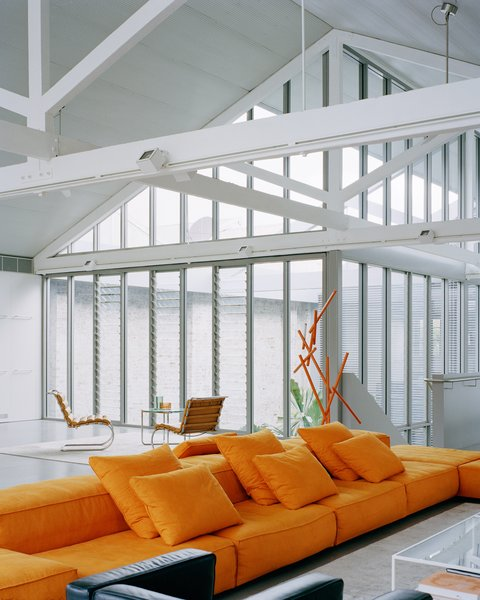 The original timber trusses are a dominant element in the living space. They had been painted white during an earlier renovation, and the design team decided to repaint them instead of stripping them back to raw timber. A new corrugated steel ceiling has been inserted between the trusses. Small perforations in the steel absorb sound into the acoustic insulation installed above.