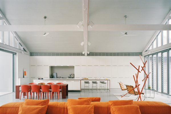 A large orange modular sofa introduces color into the interior. This warm palette is echoed to great effect in a nearby sculpture, and in other furniture throughout the living space and outdoor area.