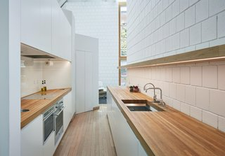 The kitchen retains its original plan, but it's been updated with new counters, cabinets, appliances, and lighting. A new wood counter, sink, cantilevered shelf, and cabinets were added opposite the original kitchen counter to create a convenient space for food and drink prep.