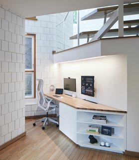 A small nook in the triangular projection of the floor plan is utilized as a home office with a custom-built desk.