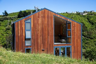 The dark blue facade is punctuated by a single cedar-clad wall that faces the deck and forms a timber nook that is protected from prevailing winds.