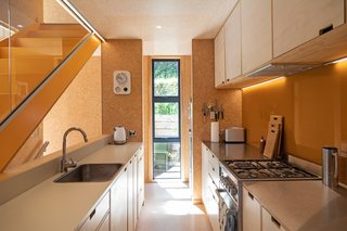 The yellow stair is echoed by a matching yellow backsplash in the kitchen.