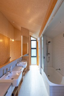 The bathroom—located upstairs—has been simply finished with white subway tiles. It's open to the dividing stair to avoid the space feeling too enclosed.