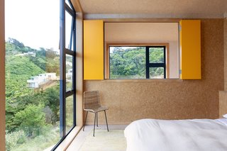 The internal bedroom windows look out over the void in the living room. The yellow shutters can be closed for privacy.