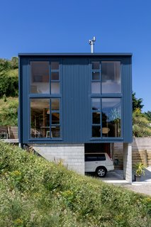 The home is elevated above a carport, which can also be used as a covered semi-outdoor living space in the summer.