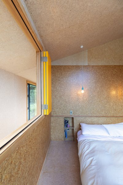 Small storage nooks are built into the walls beside the beds, avoiding the need for bedside tables.