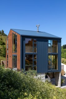The majority of the house is clad in inky blue metal—a durable, low-maintenance material.