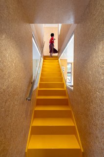 The yellow-painted stair is crafted from Kowhai, a dense and durable native timber.