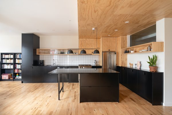 "The kitchen countertops are black quartz, offering a strong visual contrast to the plywood. ""Leïla and Xavier enjoy having friends over to sit at the kitchen island, which is the center of the space,"" says architect Catherine Milanese."
