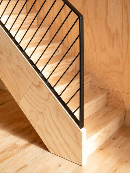 Architect Catherine Milanese wanted to use a single material—fir plywood—for the stringer, the stairs, and the risers, visually integrating the stairway with the wood box that contains the mezzanine level.