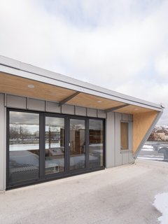 The mezzanine has rooftop access through large, south-oriented glazed doors. A steel awning offers shade to the mezzanine level during summer months, and the inside face is clad with plywood to visually extend the interior space outward.