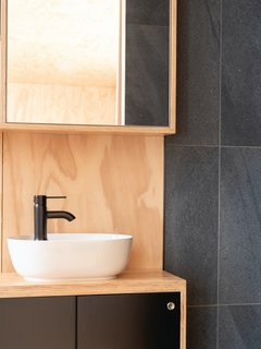 The plumbing fixtures and the dark ceramic tile reflect the black color of the cabinets. Round recessed handles are visually refined yet allow the panels on the vanity unit to be easily opened.
