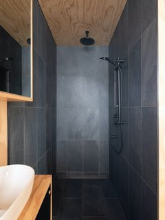 The small bathroom on the mezzanine uses the same material palette as the kitchen.