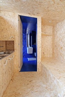 The OSB-clad living and sleeping area leads to a bold blue bathroom in this renovated home in Albino, in the Lombardy region of Northern Italy. The white fittings and fixtures in the bathroom echo the retro white cabinet handles used in the kitchen.