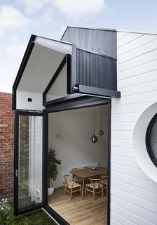 The living space extends out into the small backyard through large bifold doors. Horizontal weatherboards and vertical Mini Orb steel cladding creates a graphic, minimal rear facade that contrasts with the surrounding inner-city environment.