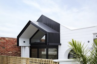 From the rear laneway, the parapet and veranda awning echo the original pitched roof, carrying the essence of the old house through to the addition.