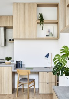 A study nook with a concrete desktop adjoins the kitchen bench, making clever use of otherwise dead space.