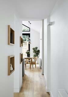 """Timber shelves in the hallway and the living room frame knickknacks and books that the client has collected over time—described by architect Aaron Neighbour as """"fragments of the owner's story""""."""