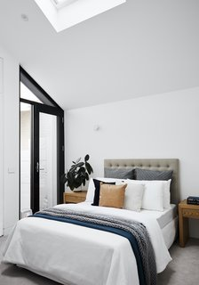 The guest bedroom is located at the front of the home, and it features both a skylight and a glazed wall section overlooking the street. A glazed door provides access to the front porch.