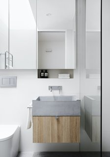 The custom bathroom sink is cast from concrete, echoing the use of concrete on the countertops in the kitchen and living area.