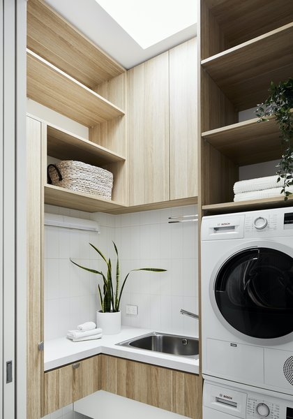 The laundry is tucked away beside the kitchen. A skylight floods the small space with natural light, and cat doors provide the resident feline with easy access to the litter box kept here.