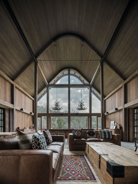 The soaring, timber-clad ceilings of the open-plan living, dining, and kitchen area follow the curve of the corrugated Zincalume roof, creating an impressive volume with views over the valley.