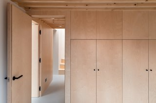 The birch plywood panelling was made off-site by the manufacturer and assembled by the builders on-site. The visual continuity of the single material makes the restricted-height storage areas appear full-height.