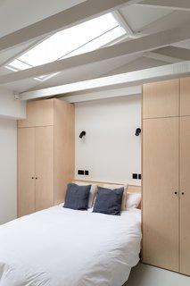 To make space for the new hallway, the existing master bedroom had to be reduced in size. To make efficient use of the smaller space, BVDS Architecture designed fitted wardrobes either side and over the double bed. An existing flat ceiling was also removed to open up the space and create more volume.