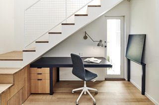 The study nook features a long desk that provides access to the home's side entrance when partially folded up.