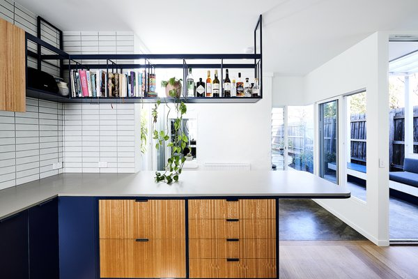 Custom steel shelving suspended above the kitchen island brings an industrial aesthetic to the interior that compliments the facade of the dairy, which is symbolic of an industrious era.