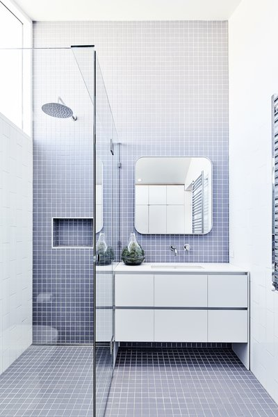The bathrooms feature a clean, minimal blue-and-white palette, with a focus on durable, functional materials.
