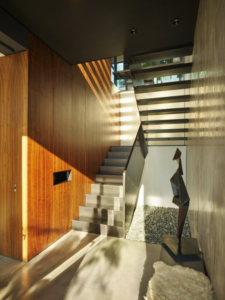 The central stair sits against a three-story mahogany cabinet that houses a powder room, a study, and a multitude of closets.