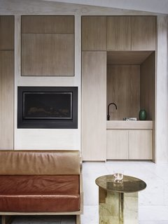 In the kitchen, oak joinery and a minimal fireplace sit within a neutral, low-cost pine plywood wall.