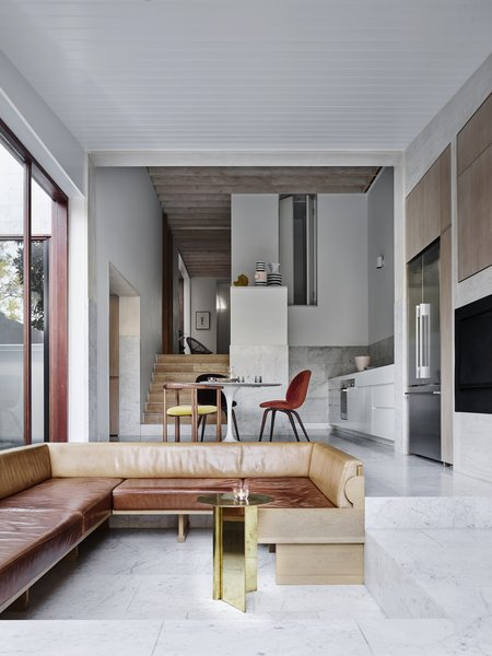 """A gentle site crossfall offered an opportunity to experiment with internal level changes. """"I just loved the idea of a conversation pit,"""" says architect Jeremy Bull. """"It is a quirky oak and leather bench which gets used for most of our sitting, meals, board games, and spilling things."""""""