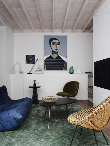 The casual living room on the ground floor features a vintage cane chair, a Togo sofa by Michel Ducaroy for Ligne Roset, and a portrait titled Matriarch by contemporary Danish artist Henrik Godsk.