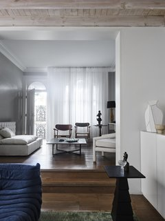 The two living rooms at the front of the home sit on slightly different levels. The more formal living room features a linen sofa by Pure Interiors and classic CH22 and CH26 timber chairs by Hans J. Wegner for Carl Hansen & Son.