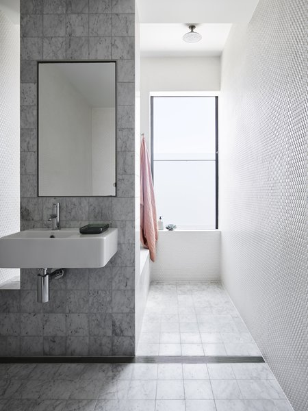 Carrera marble tiles in four different scales can be found throughout the home—including in the bathroom, the kitchen and sunken lounge, and the backsplash.