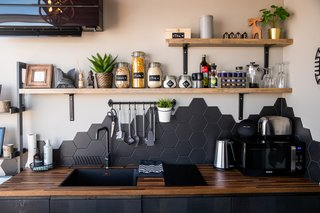 "The kitchen features oak woodwork, black fixtures and fittings, and black hexagonal tiles that mimic the lines of the local landscape and represent the ""basalt columns and moodiness of Iceland""."