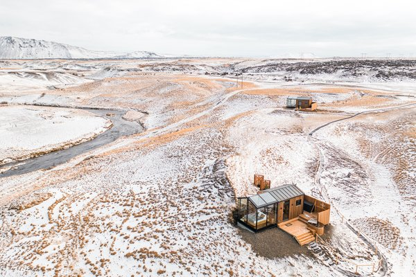 Two cabins sit in the vast, empty landscape overlooking the Hekla volcano, around three hours' drive from Reykjavík. The front part of each cabin—for sleeping—is almost entirely glass, while the rear—where the living, kitchen and bathroom spaces are located—is clad in timber for privacy.