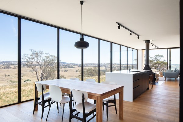 The open-plan dining area, kitchen, and living room are arranged in the living wing. The dining and living spaces are separated by the kitchen island and fireplace, so each functional zone is clearly defined. There are also plenty of breakout spaces that cater to a wide range of activities.