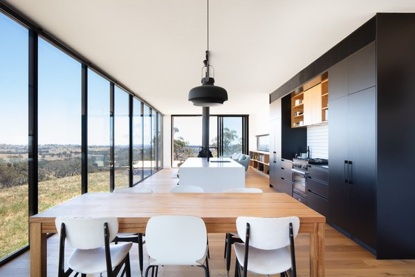 The kitchen is at the heart of the home, and the layout is arranged so that the views can be appreciated when preparing a meal. Warm timber shelves and furniture contrast with the dark kitchen joinery to create a balanced interior palette.
