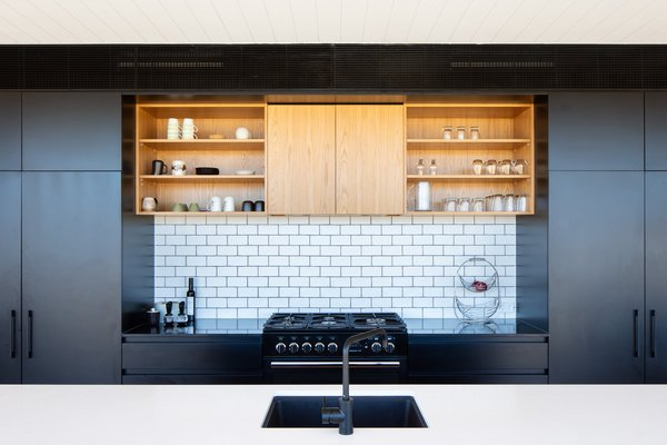 The handmade-look white brick tiles on the kitchen backsplash echo the brickwork used on the outdoor fireplace. They help to provide visual continuity from the exterior to the interior.