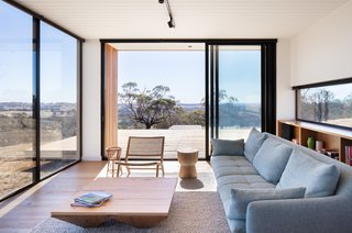 A deck opens up to the west from the main living space, and it's the perfect place to watch the sunset. A long, low window at the rear of the space frames the tree line.